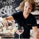 Der Barkeeper mixt an der Theke einen Gin Tonic.