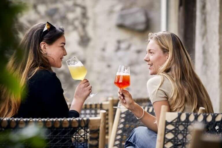 Besucherinnen trinken im großen Biergarten den Decantei-Aperitif