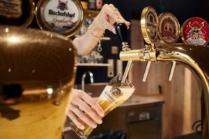 Eine Barkeeperin schenkt an der Bar in Brixen ein Bier ein.