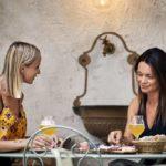 Zwei Frauen sitzen im Biergaren, trinken ein Bier und essen eine Jause.