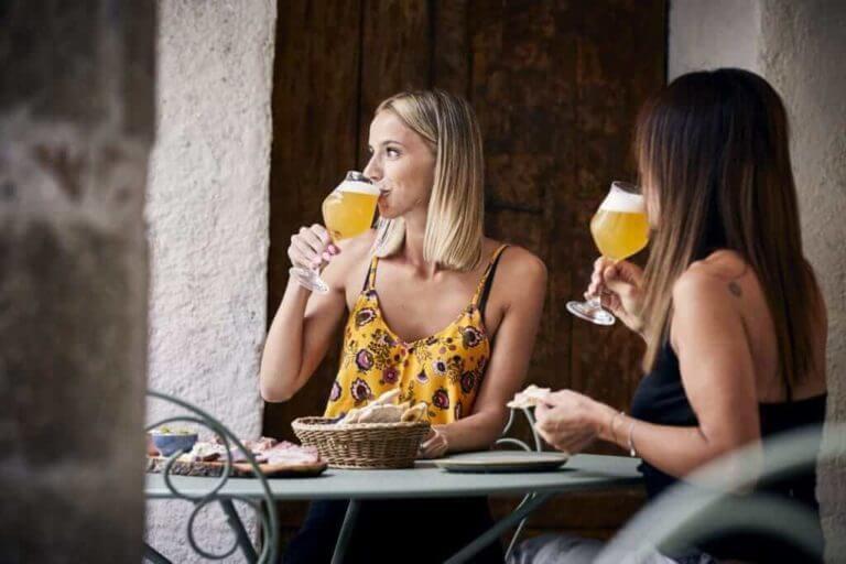 Zwei Frauen sitzen draußen, essen eine Bauernplatte und trinken dazu ein Bier.