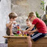 Drei Kinder spielen im Sandkasten mit Blauklötze und haben ersichtlich Spass.